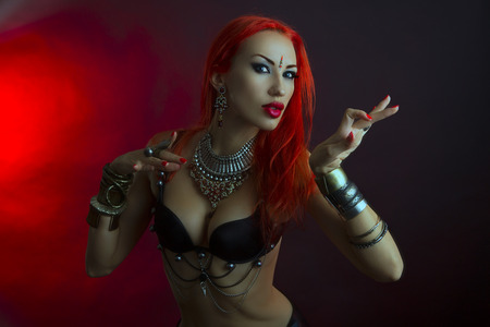 bellydance: Bellydance, Tribal Fusion. Beautiful Redhead Young Woman in Sexy Clothing with Eastern Makeup and Luxury Oriental Jewelry. Beautiful Girl Hot Bollywood Dancer (Sensitive Bellydancer). Eastern fairy tale, Harem. Stock Photo