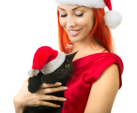 red animal: Beautiful Joyful Sexy Smiling Woman in Red Santa Claus Hat with Funny Black Cat Santa - Cute Christmas Cat, Christmas pet with Santa Claus hat. Isolated on white. Happy Christmas and New Year Holidays