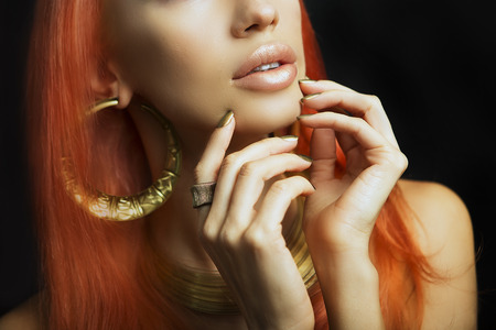 lip: Beautiful Women Lips with Stylish Golden Shiny Lipstick and Hands with Golden Manicure and Gold Jewelry on dark background.  Stock Photo
