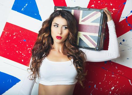 bandera inglaterra: joven y bella mujer linda que presenta con la maleta. Mujer joven que se coloca con la bandera del Reino Unido en el fondo. Un viaje a Inglaterra en Londres, viajes y estudios. concepto de aprendizaje de idiomas Inglés