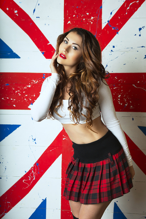 student travel: Beautiful Cute Young Woman cheerleader standing with the UK flag in the background. A Trip to England in London, Travel and Study. English language learning concept Stock Photo
