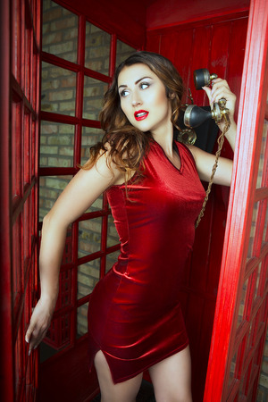 retro telephone: Beautiful Cute young Woman posing with retro phone in a red UK Phone Cabine in London. A Trip to England in London. Telephone call Stock Photo