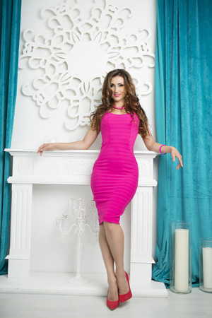 full height: Beautiful Sexy Glamour Brunette Woman in Pink fashionable Dress and red Shoes with Heels Posing in white Luxury Stylish Interior. Trendy look, Full height