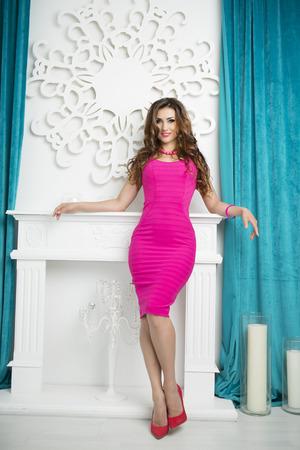 Hermosa Sexy Glamour Mujer Morena en rosa vestido de moda y zapatos rojos con los talones posando en blanco con estilo de lujo Interior. Aspecto moderno, de altura completa Foto de archivo
