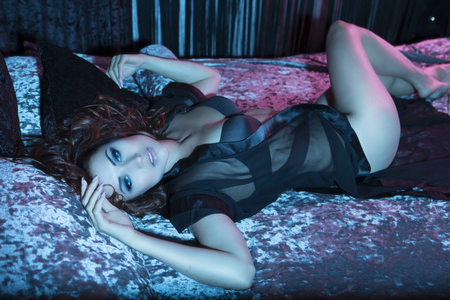 Beautiful Sexy Glamour Brunette Woman Lying in Bed in the bedroom in Sensual Black transparent Peignoir (lingerie). Luxury Stylish Interior with Blue light. Night or Evening