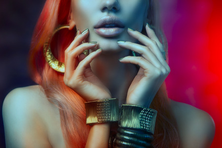 Beautiful Women Lips with Stylish Golden Shiny Lipstick, Golden Manicure and Gold Jewelery on Red Background. Glamor Creative Art Portrait. Makeup, Fashion, Beauty, Hairstyle. High Fashion Youth Look. Colorful Rainbow Style Banque d'images
