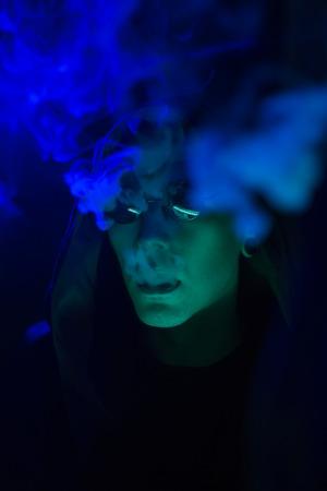 youth smoking: Partido del club - Vida nocturna. Hermoso atractivo hombre joven con estilo en vidrios negro fumar en Discoteca Chill-out. Creativa mirada fresca juventud. Fiesta casera. filtros de color, enfoque suave. Retrato en un ambiente m�stico
