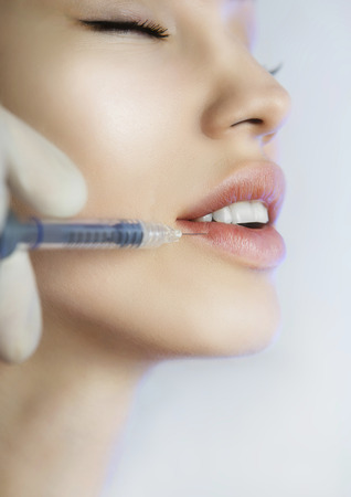 procedures: Young Woman Gets an Injection in her Lips in Beauty salon. Beauty Injections -Woman lying in the beautician office. Increase the Lips by Hyaluronic acid, Contouring procedure, revitalization Stock Photo