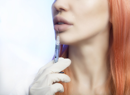 augmentation: Young Woman Geting an Injection in her Lips. Beauty Injections -Woman wondered about methods lip augmentation in the beautician office. Increase the Lips by Hyaluronic acid, Contouring procedure, revitalization