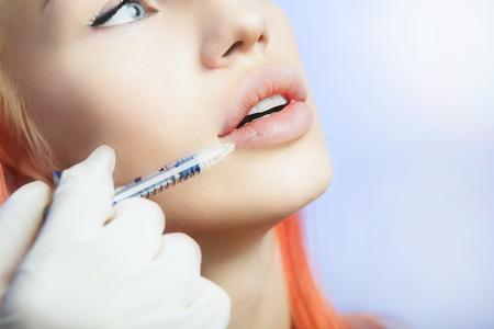 skönhet: Ung kvinna Geting en injektion läpparna i skönhetssalong. Skönhet Injektioner -Woman liggande i kosmetolog kontoret. Öka Lips av Hyaluronsyra, kontur förfarande, vitalisering Stockfoto