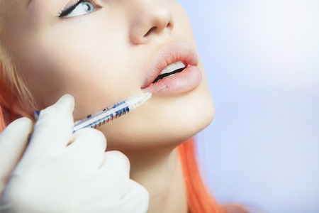 the caucasian beauty: Young Woman Geting an Injection in her Lips in Beauty salon. Beauty Injections -Woman lying in the beautician office. Increase the Lips by Hyaluronic acid, Contouring procedure, revitalization