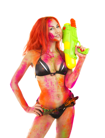 Happy Holi Festival! Holi Celebration Party - Beautiful Sexy Caucasian Girl in bikini with toy gun colored Dry Bright Multicolor Paint Powder on White background keep Indian traditional spring color Festival