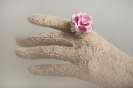 lace gloves: Romantic vintage retro style: Polymer clay jewelery: Fashion studio blurred  shot of Female hand in lace gloves with a beautiful rose floral ring. Spring - Summer fashionable accessories, soft focus