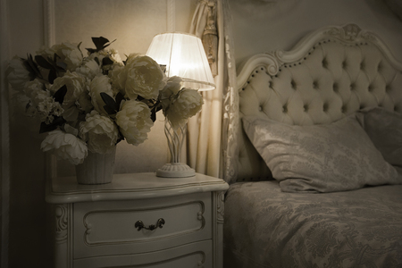 luxuriously: Luxury Royal Interior. Luxurious bed with cushion and stand lamp in royal bedroom interior. Vintage decor elements in the bedroom. Nightlight and elegant vase on the bedside table. monochrome filter