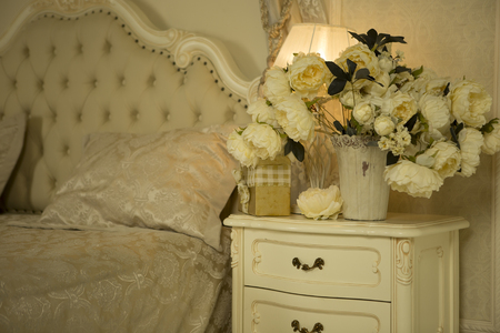 painted: Luxury Royal Interior. Luxurious bed with cushion and stand lamp in royal bedroom interior. Vintage decor elements in the bedroom. Nightlight and elegant vase on the bedside table.