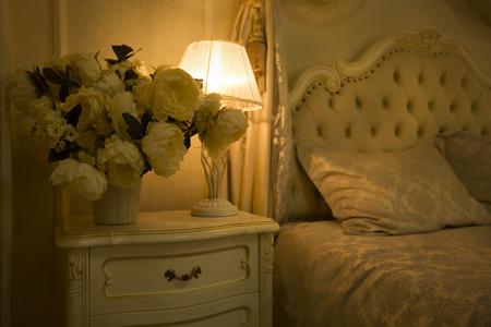 luxuriously: Luxury Royal Interior. Luxurious bed with cushion and stand lamp in royal bedroom interior. Vintage decor elements in the bedroom. Nightlight and elegant vase on the bedside table.