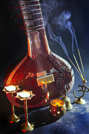Sitar, a String Traditional Indian Musical Instrument, close-up, blue lens effect. dark background with incense smoke. Evening of ethnic oriental music. Indian Raga
