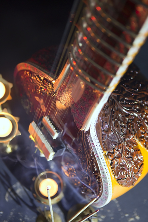shankar: Sitar, a String Traditional Indian Musical Instrument, close-up, blue lens effect. dark background with incense smoke (soft focus). Evening of ethnic oriental music. Indian Raga