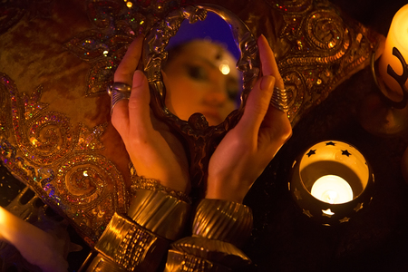 arabian harem: Golden Oriental Jewelry and Accessories: Female Hands with beautiful Indian Jewellery, Eastern Fairy Tale (Harem), Wedding Fashion.  Beauty woman with mirror by Candlelight. Luxury Arabian details Stock Photo