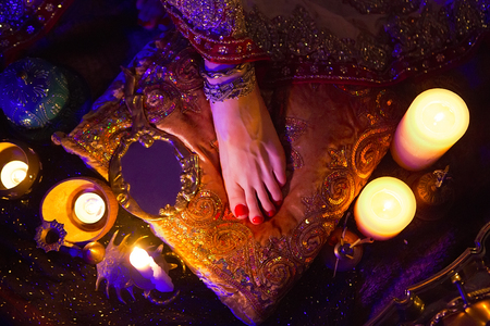 bollywood woman: Indian Wedding Preparation. Luxury Oriental Fashion Accessories: Female foot, Beautiful National Indian Bridal Golden Jewellery. Eastern Traditional Sari clothes. Color lenses, Candlelight, soft focus Stock Photo