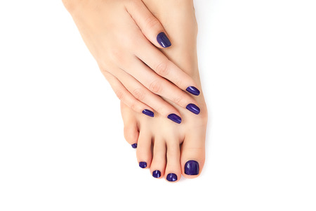 purple manicure and pedicure. Makeup, fashion, beauty. Beautiful female legs with purple pedicure and hands with purple manicure