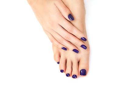 paarse manicure en pedicure. Make-up, mode, schoonheid. Mooie vrouwelijke benen met paarse pedicure en handen met paarse manicure Stockfoto