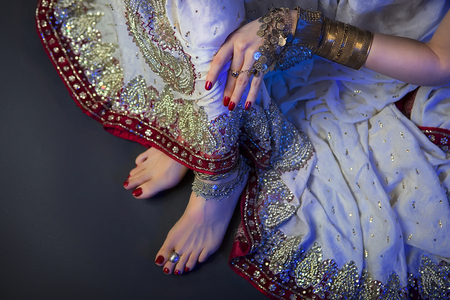 Indian Wedding Preparation. Luxury Oriental Fashion beauty Accessories: Female foot, Beautiful National Indian Bridal Golden Jewellery. Eastern Traditional Sari clothes. Blue filter, dark background