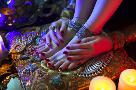 rich woman: Indian Wedding Preparation. Luxury Oriental Fashion Accessories: Female foot and Hands, Beautiful National Indian Bridal Golden Jewellery. Eastern Traditional Sari clothes. Color lenses, Candlelight Stock Photo