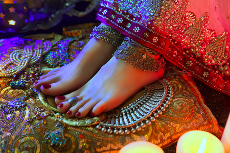 bollywood woman: Indian Wedding Preparation. Luxury Oriental Fashion Accessories: Female foot with anklets. Beautiful National Indian Bridal Golden Jewellery. Eastern Traditional Sari clothes. Color lenses, Candlelight Stock Photo