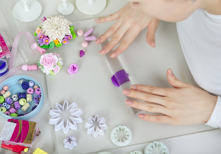 clays: Artist makes jewelry from color Polymer Clay, artist at work. Workshop. Hobby – Art Clay Modeling. Tools for Modeling. Handmade Production. Plasticine. Hands rolled plastic Stock Photo