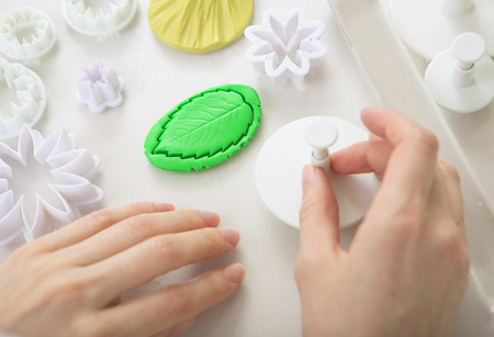 clay modeling: Artist makes Polymer Clay jewelry, artist at work. Workshop. Hobby � Art Clay Modeling. Tools for modeling. Handmade Production. Plasticine. Hands using the template stamp (preform)
