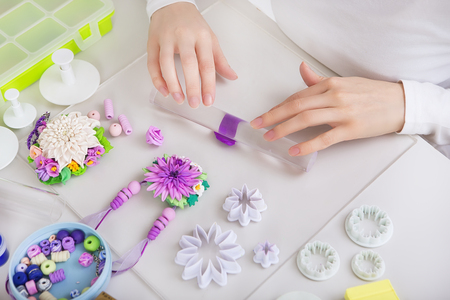 clay modeling: Artist makes jewelry from color Polymer Clay, artist at work. Workshop. Hobby – Art Clay Modeling. Tools for Modeling. Handmade Production. Plasticine. Hands rolled plastic Stock Photo