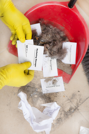Staff reduction concept - Cutting staff and employee Job Reduction. Dismissal. Office cleaner throw in the debris staff business cards. Crisis management and HR policy. Marketing Manager hire Stock Photo