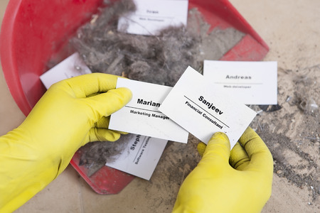 dismissal: Staff reduction concept - Cutting staff and employee Job Reduction. Dismissal. Office cleaner throw in the debris staff business cards. Crisis management and HR policy. Financial Consultant hire Stock Photo