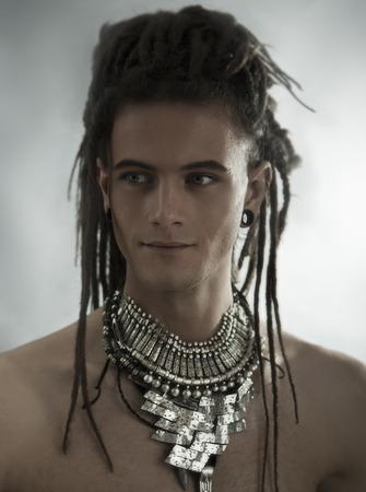 dreadlocks: Retrato de hombre joven. Individuo con estilo atractivo hermoso con Dreadlocks y joyería étnica, Accesorios (collar, pulsera, anillo) Primer plano de la cara. Estilo tribal. mirada de moda del hombre joven