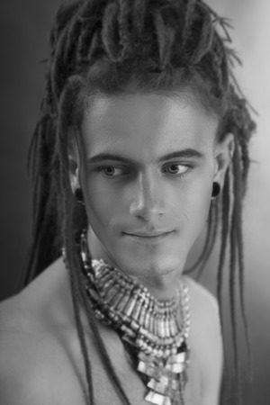 youthful: Young mans portrait. Stylish handsome sexy Guy with Dreadlocks and ethnic Jewelry, Accessories (necklace, bracelet, ring) Close-up face. Tribal Style. Trendy youthful mans look