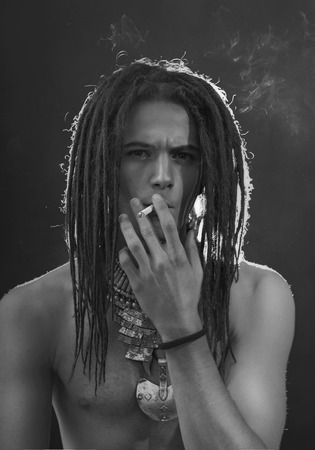goodly: Young mans portrait. Stylish handsome sexy Guy with Dreadlocks and ethnic Jewelry, Accessories (necklace, bracelet, ring) Close-up face. Tribal Style. Trendy youthful mans look