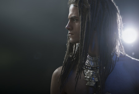 Young man's portrait. Stylish handsome sexy Guy with Dreadlocks and ethnic Jewelry, Accessories (necklace) Close-up face. Tribal Style. Trendy youthful man's look, warrior. War paint