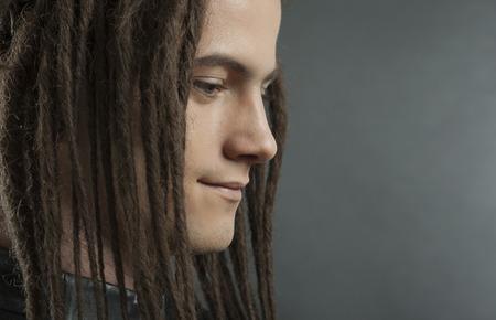 dreadlocks: Retrato de hombre joven. Individuo con estilo atractivo hermoso con Dreadlocks en la chaqueta de moda de cuero negro, Primer plano de la cara. Estilo tribal. mirada de moda del hombre joven