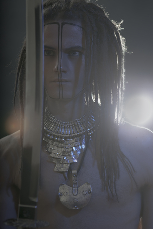 goodly: Young mans portrait. Stylish handsome sexy Guy with Dreadlocks and ethnic Jewelry, Accessories (necklace, bracelet) Close-up face. Tribal Style. Trendy youthful mans look with katana sword Stock Photo