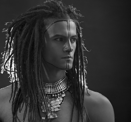 Young mans portrait. Stylish handsome sexy Guy with Dreadlocks and ethnic Jewelry, Accessories (necklace, bracelet) Close-up face. Tribal Style. Trendy youthful mans look, war paint