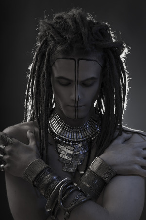 goodly: Young mans portrait. Stylish handsome sexy Guy with Dreadlocks and ethnic Jewelry, Accessories (necklace, bracelet) Close-up face. Tribal Style. Trendy egypt youthful mans look, war paint Stock Photo
