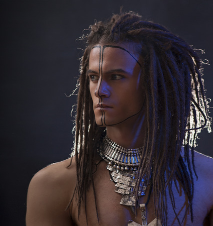 goodly: Young mans portrait. Stylish handsome sexy Guy with Dreadlocks and ethnic Jewelry, Accessories (necklace, bracelet) Close-up face. Tribal Style. Trendy youthful mans look, war paint