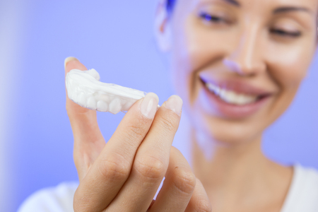 a tooth are beautiful: Beautiful Smiling Girl with Tooth Tray (hands Holding Individual Tooth Tray), Methods of Teeth Teeth Whitening and Correction, Close-up (blue filter effect)