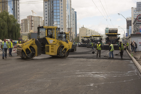 crawler: Kyiv, Ukraine Jul 2016: Road Paving, construction. Workers laying stone mastic asphalt during street repairing works 2016 in Kyiv on Peremogy ave - One of the central roads of Kiev