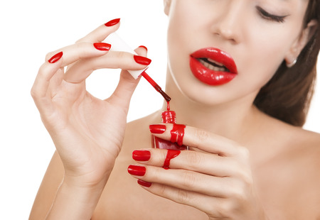 Manicure process - Sexy Young Beautiful Girl with Red Nails and lips making manicure messy (self manicure mistakes). Sensual bright sloppy Make-up. Youth trendy fashion look. Flowing nail polish
