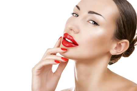 sexualidad: Atractiva joven hermosa niña morena con uñas de color rojo y el lápiz labial rojo. Retrato femenino del encanto, sensual maquillaje brillante y primer de la manicura. Jóvenes look de moda de moda. Fondo blanco