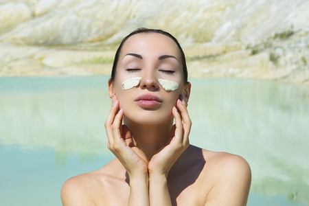 Woman with Blue Clay Facial Mask. Beauty and Wellness. Spa Outdoor, Beautiful Young Woman with natural Dead Sea Facial Mask on her Face near the Lake with Blue and White Cosmetic Healing Clay