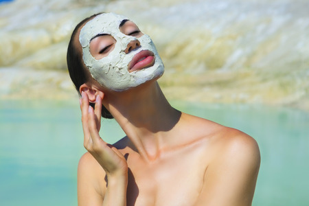 mud woman: Woman with Blue Clay Facial Mask. Beauty and Wellness. Spa Outdoor, Beautiful Young Woman with natural Dead Sea Facial Mask on her Face near the Lake with Blue and White Cosmetic Healing Clay