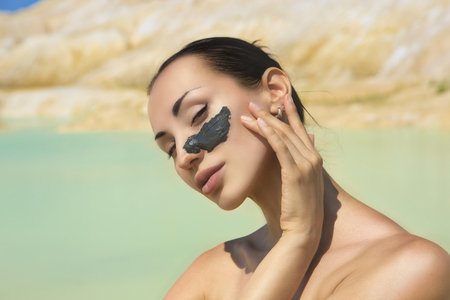 Woman with black Clay Facial Mask. Beauty and Wellness. Spa Outdoor, Beautiful Young Woman with natural Dead Sea Facial Mask on her Face near the Lake with Blue and White Cosmetic Healing Clay